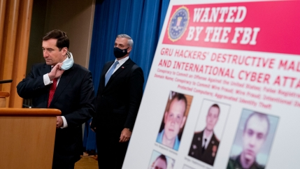 A poster showing six wanted Russian military intelligence officers is displayed as Assistant Attorney General for the National Security Division John Demers, left, takes the podium to speak at a news conference at the Department of Justice, Oct. 19, 2020.