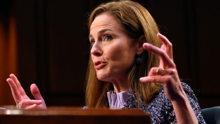 Judge Amy Coney Barrett speaks and gestures into a mic during the third day of her Senate confirmation hearing.