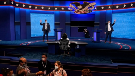 Two men are shown on the debate stage wearing face masks and pretending to wave to an audience.