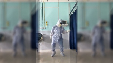 Dr. Arup Senapati is shown in full medical personal protective equipment and dancing in a hospital.
