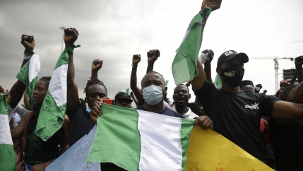 People hold banners as they demonstrate on the street to protest against police brutality in Lagos, Nigeria, Oct. 19, 2020.