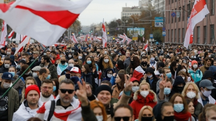 A large crowd of people are shown filling a square with many holding old Belarusian flags.