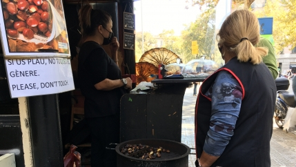 A woman wearing a face mask sells roasted chestnuts as another woman wearing a blue apron minds the chestnuts.