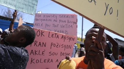 Two Haitians protest with a pink sign against UN peacekeeping mission that caused a massive cholera epidemic.