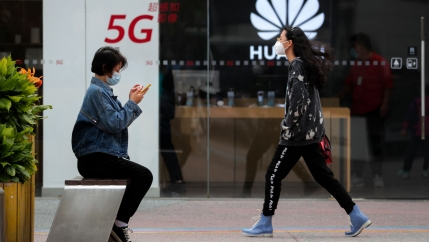 A woman wearing a jean jacket is shown sitting on a bench as anothe woman walks toward her with the clear glass of a Huawei store in the distance.