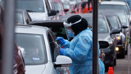 A nurse takes a swab sample at a drive-through coronavirus test site at the University of Texas El Paso in El Paso, Texas, Oct. 27, 2020.