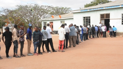 A long line of people are shown standing outside of a polling location in Tanzania.