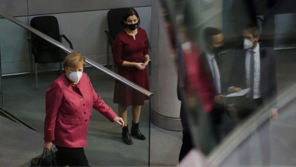 German Chancellor Angela Merkel is shown walking with a briefcase and wearing a red jacket with a woman behind her wearing a dark red dress.