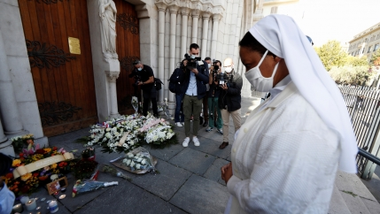 A nun prays in front of candles and flowers left in tribute to the victims of a deadly knife attack at the Notre Dame church in Nice, France, Oct. 30, 2020.