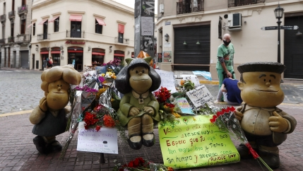 A woman mourns the death of cartoonist Joaquin Salvador Lavado, also known as Quino, who died yesterday at the age of 88, as flowers and tributes are seen next to sculptures of comic characters Mafalda, Susanita, and Manolito, created by him, in Buenos Ai