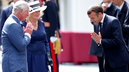 Prince Charles, the Duchess of Cornwall, and Emmanuel Macron greet each other with a 'namaste' on an airport tarmac