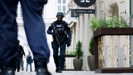Several heavily armed police officers are shown walking on a street in Vienna with one officer passing a bar.