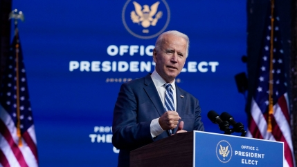 US President-elect Joe Biden is shown standing at a podium with microphones in front of a backdrop that says,