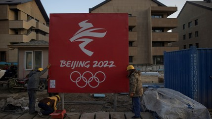 Workers move a sign at the Olympic Village for the 2022 Winter Olympics in the Chongli district of Zhangjiakou, Hebei province, China, Oct. 29, 2020.