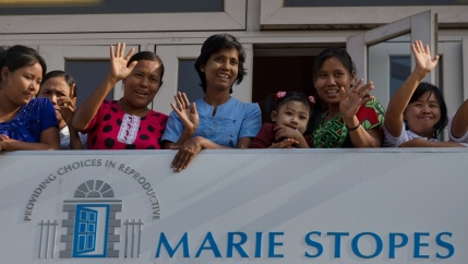 Patients and staff members of Marie Stopes International (MSI) Clinic wave to Danish delegation members.