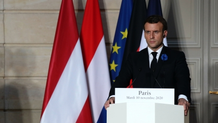 French President Emmanuel Macron stands at a podium with French flag behind him.