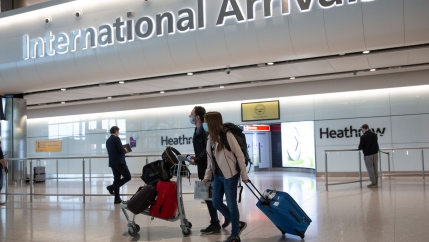A pair of travelers are shown walking in the International Arrivals section of London's Heathrow Airport with one person pushing a cart carrying several bags.