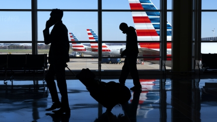Wearing masks, travelers walk to and from their planes at Ronald Reagan Washington National Airport, Nov. 24, 2020, in Arlington, Virginia, in advance of the Thanksgiving holiday.