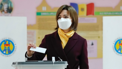 A woman wearing a suit with yellow shirt casts a ballot while wearing a mask