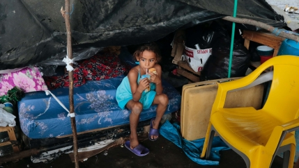 A young girl wearing light blue clothing sips a juice while sitting inside a shelter near a yellow plastic chair