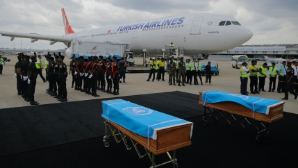 Two caskets covered with UN flags on display near a Turkish airlines plane and military personel standing nearby.