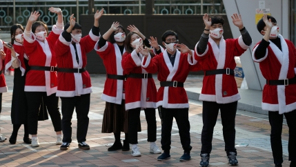 Volunteers wearing face masks wave after they load boxes onto a delivery truck during an event to send Christmas gifts for the underprivileged in Seoul, South Korea, Dec. 22, 2020.