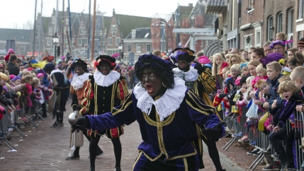 Dutch white people in blackface and colorful costumes