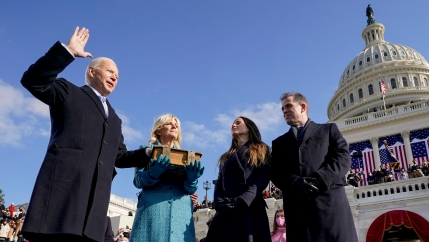 Joe Biden is shown with his right hand in the air and his left hand on a bible as he is sworn in as the 46th president of the United States.