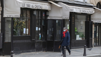 A person walks past a closed restaurant in Paris wearing a face mask.