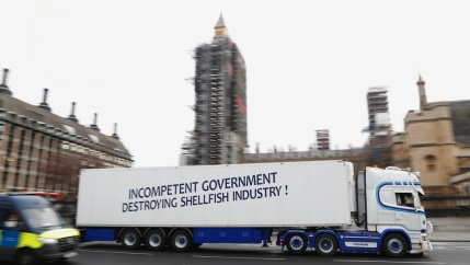 A shellfish export truck with a protest sign written across the trailer