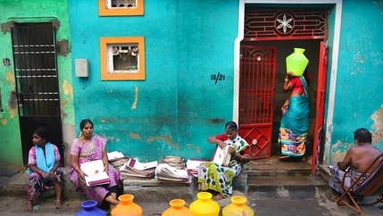Several women in colorful saris sit and stand with bright yellow drinking vessels in front of a blue and green painted building.