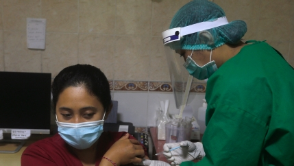 A health worker gives an injection to a mock patient during a coronavirus vaccine drill in Bali, Indonesia.