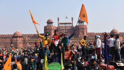 Sikhs wave the Nishan Sahib, a Sikh religious flag, as they arrive at the historic Red Fort monument in New Delhi, India, onTuesday, Jan. 26, 2021.