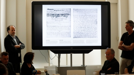 Two men stand on both sides of a projector screen, displaying pages of Anne Frank's handwriting.