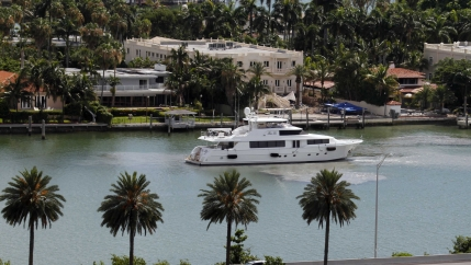 A yacht maneuvers near homes on Palm Island