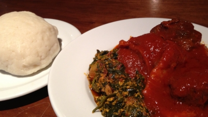 A plate of white fufu with another plate of food with red sauce