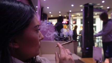 A woman smokes a joint at cannabis coffee shop Prix d'Ami in Amsterdam, Netherlands, March 13, 2020.