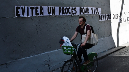 A man rides a bike by a slogan pasted on a wall reading