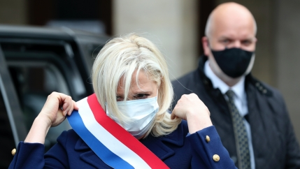 A white woman wearing a face mask also wears a red, white and blue sash around her chest and a man with a black mask stands behind her.
