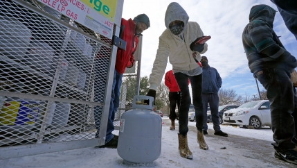 A woman is shown bending over with a white propane tank in her hand and wearing a hooded jacket.