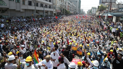 Thousands of people are shown marching in a street with many wearing yellow construction helmets.