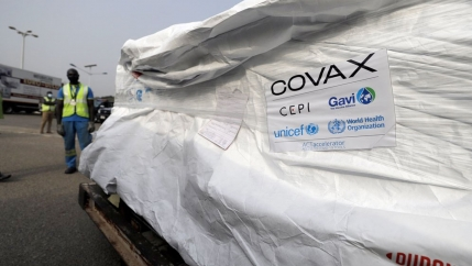 A large pallet is shown covered in a white wrapping with the logo for COVAX posted on the side.