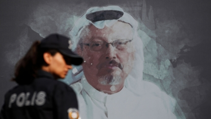 A police officer is shown looking over her right shoulder and wearing a hat with a portrait of slain Saudi journalist Jamal Khashoggi on the wall behind her.