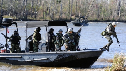 Navy soldiers in training unload a boat during a field training exercise.
