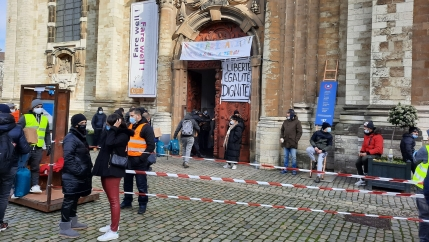 People stand in front of a church door with protest signs on it.