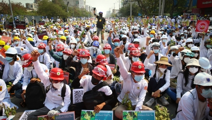 A large crowd of protesters are shown, many wearing construction hard hats and with their fist raised in the air.