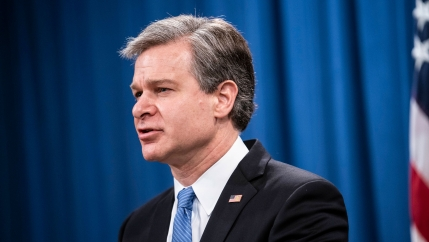 FBI Director Christopher Wray is shown wearing a dark suit and blue striped tie with a US flag pin on his lapel.