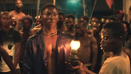 Two young Ivory Coast men stand in a crowded prison with a small lantern lit.
