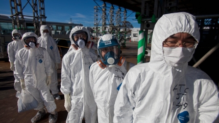 In this Nov. 12, 2011 file photo, workers in protective suits and masks wait to enter the emergency operation center at the crippled Fukushima Daiichi nuclear power station in Okuma, Japan.