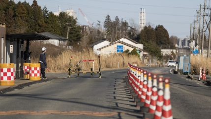 Security guards look at outbound vehicles moving toward them at a security checkpoint where part of the Fukushima Daiichi nuclear power plant is seen in the background in Okuma town in Fukushima prefecture, northeastern Japan, Feb. 25, 2021. An official